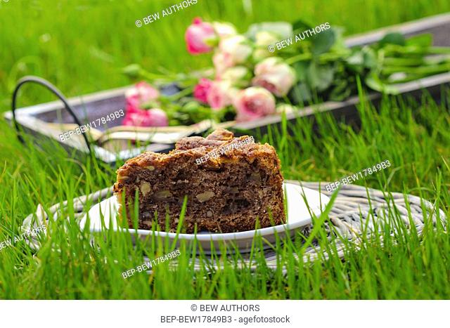 Piece of chocolate cake, bouquet of pink roses in the background. Selective focus