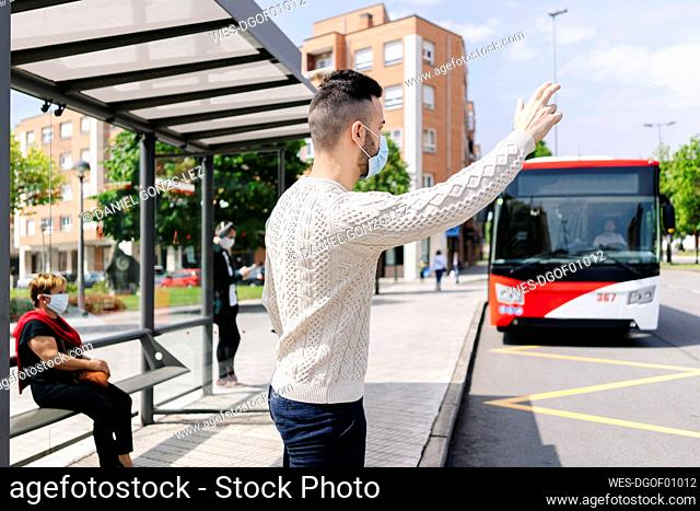 Man wearing protective mask standing at bus stop hailing taxi, Spain