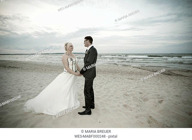 Germany, Mecklenburg-Western Pomerania, Ruegen, Sellin, bridal couple standing hand in hand on the beach