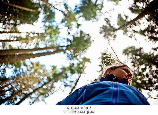 Woman with trees, low angle view
