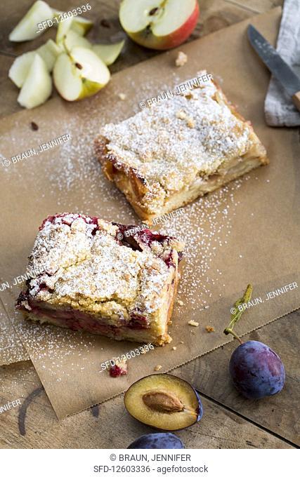 A slice of apple tray bake cake and a slice of damson tray bake cake