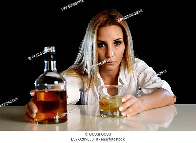 drunk woman alone in wasted and depressed face expression with scotch whiskey bottle and glass isolated on black background in alcohol abuse and alcoholic...