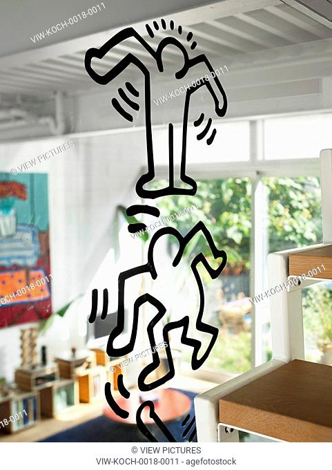 Keith Haring sticker on the glass screen between staircase and living room. 174 Grand Street, New York, United States. Architect: Loadingdock 5 Architecture