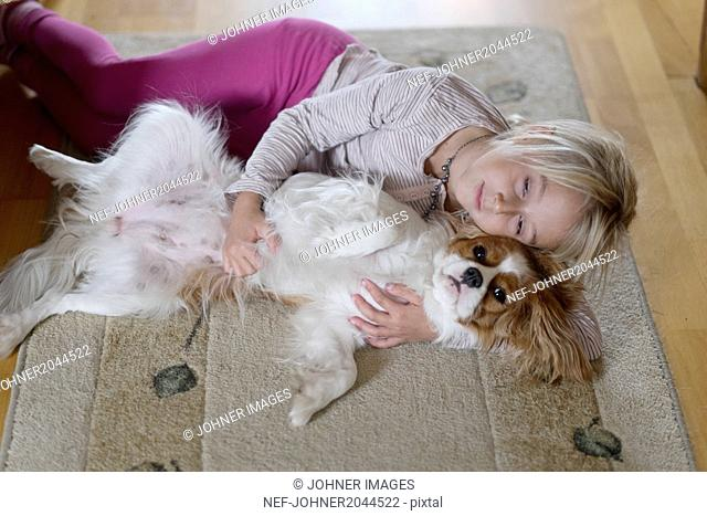 Girl lying with dog on carpet