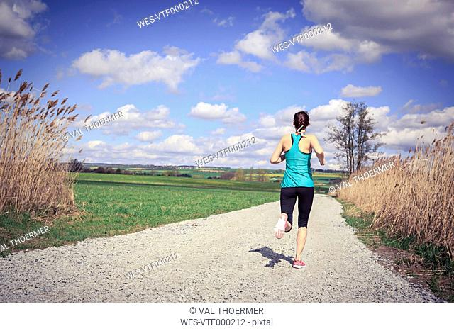Woman jogging through the rural landscape