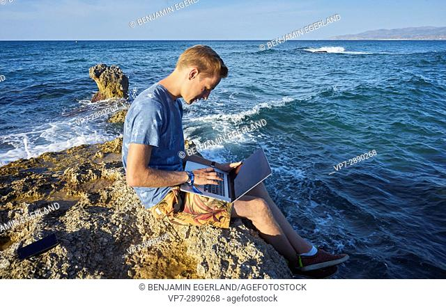 young man using laptop computer next to sea in holiday location Hersonissos, Crete, Greece