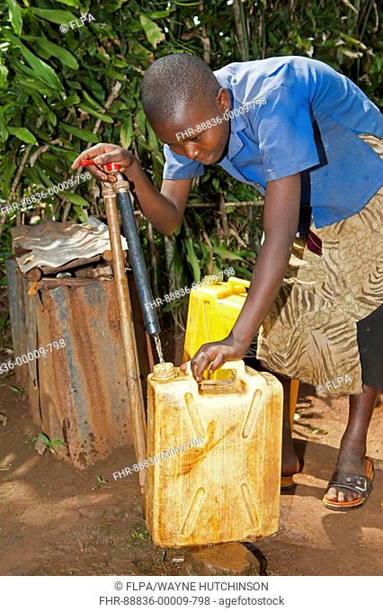 Rwandan girl filling container with fresh water from a tap