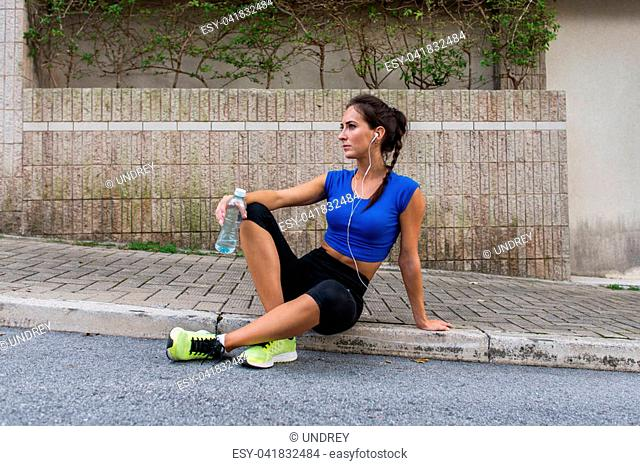 Young athletic female resting after running exercise, listening to music in earphones, holding a bottle of water, sitting on a sidewalk on city street