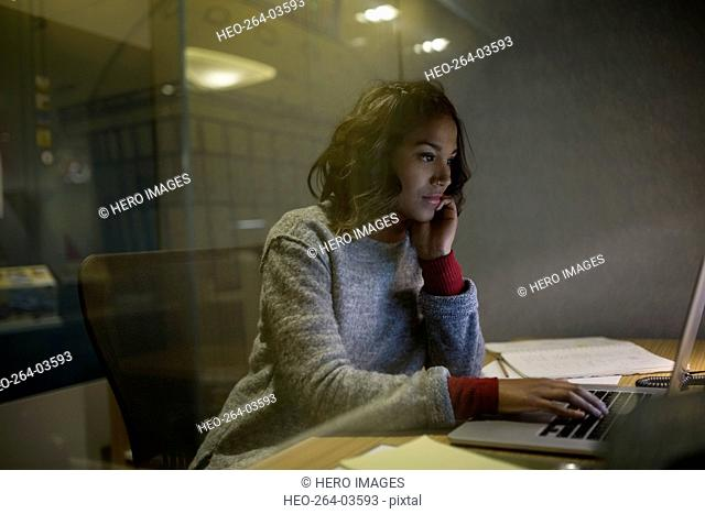 Focused young businesswoman working late at laptop