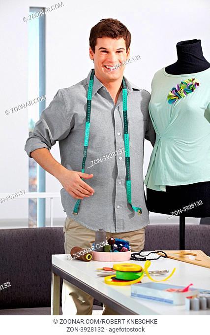 Lachender Modedesigner steht mit Schneiderpuppe in seinem Atelier