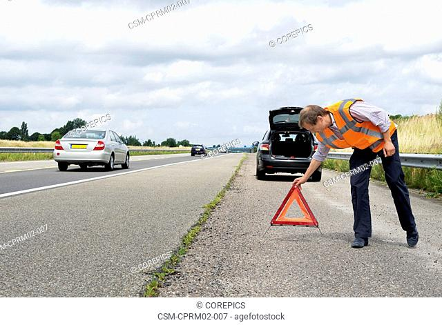 Motorist, placing a warning triangle behind his broken down car on the side of a motorway, with cars passing