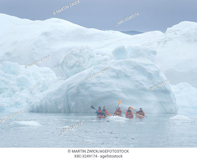 Kayak in fog in front of huge icebergs. Ilulissat Icefjord also called kangia or Ilulissat Kangerlua at Disko Bay. The icefjord is listed as UNESCO world...