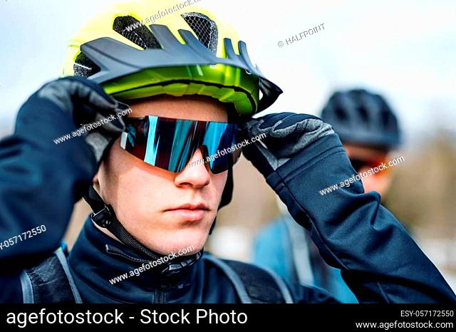 Two mountain bikers standing on road outdoors in winter, putting on sunglasses