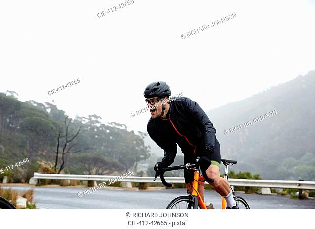 Determined male cyclist powering uphill