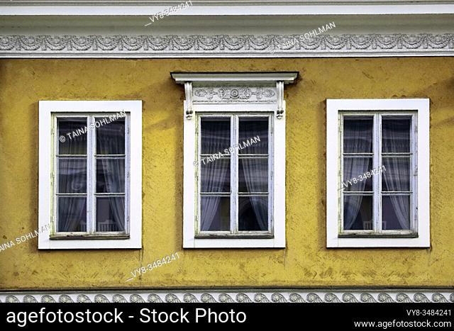 Detail of three windows on the exterior of a yellow classic, historic city building. Digital art image