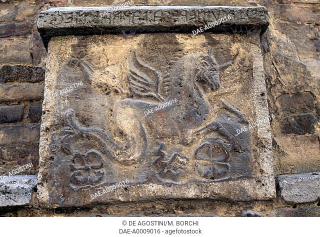 Winged horse, relief on the base of Palazzo Bucelli inlaid with stone fragments, cinerary urns, Etruscan and Roman inscriptions, Montepulciano, Tuscany, Italy