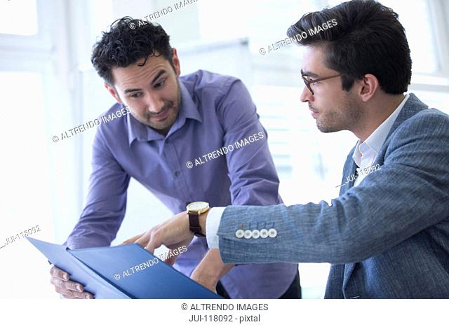 Two Businessmen Discussing Document In Office Together