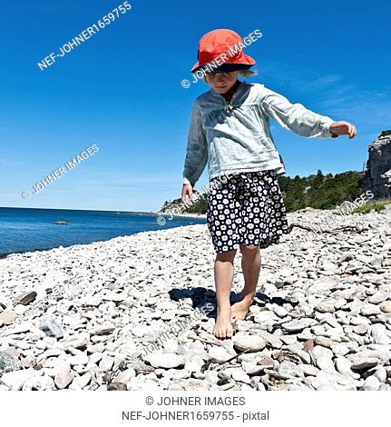Girl walking on pebble beach