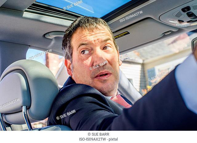 Business man in car looking over shoulder