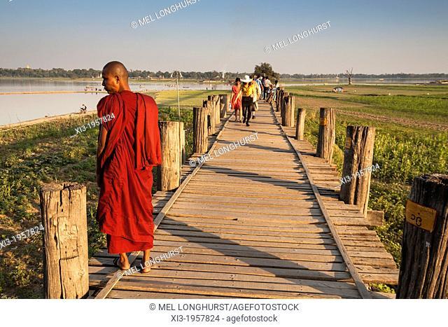 Buddhist monk standing on U Bein wooden bridge, Taungthaman Lake, Amarapura, Mandalay, Myanmar, (Burma)