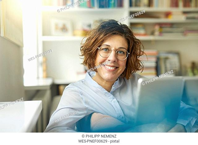 Portrait of content mature woman with tablet at home
