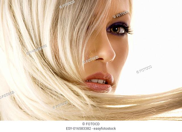 close-up of face of pretty girl with long blond hair watching in camera