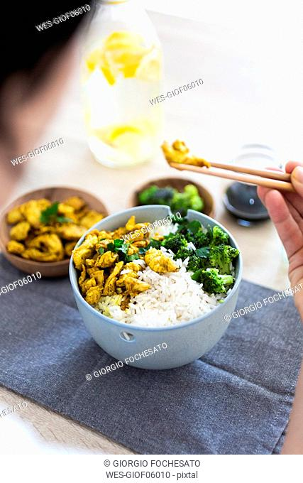 Curry chicken, broccoli and rice, woman eating with chopsticks