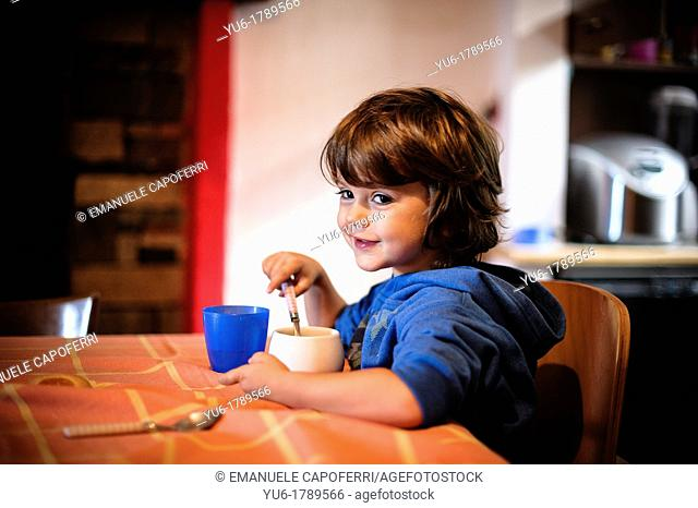 Child gets breakfast sitting at the kitchen table