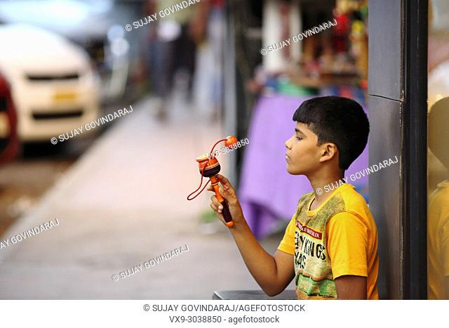 Bangalore, India - October 16, 2016: Unknown kid sitting aside a shop spotted playing with his toy in Brigade Road, Bangalore
