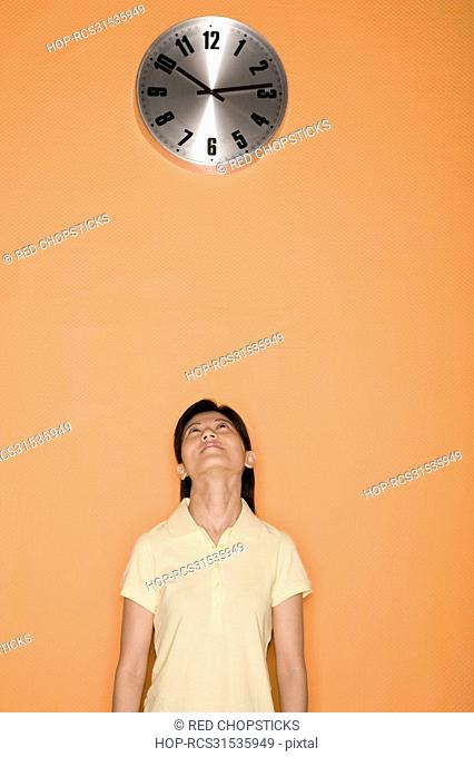 Female office worker looking at a clock