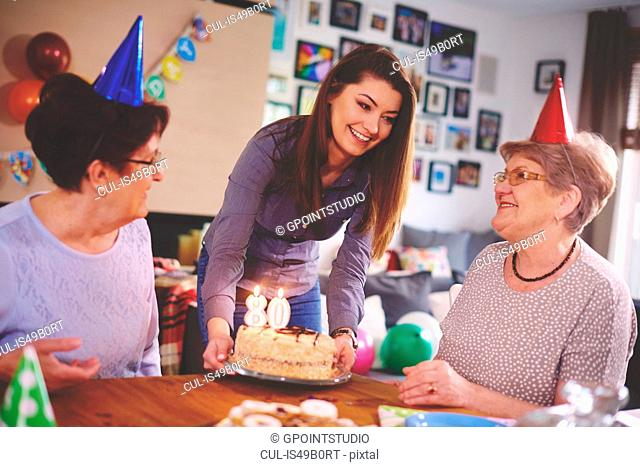 Daughter presenting birthday cake to mother at birthday party