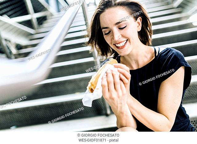 Smiling woman with Hot Dog sitting on stairs