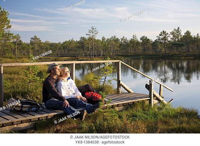 Young Couple Sitting on Wooden Boardwalk by Water in Meenikunno Landscape Reserve, Estonia