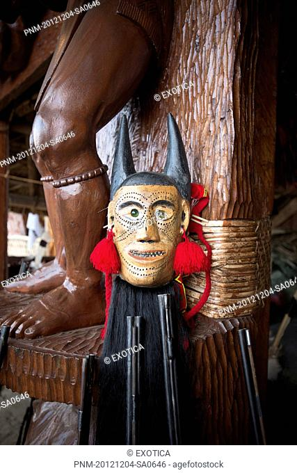 Mask with guns and wooden statue in a tribal hut, Kohima, Nagaland, India