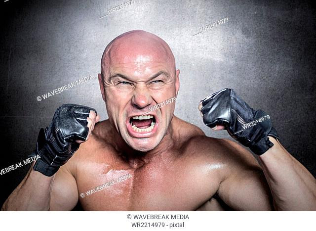 Composite image of angry fighter with gloves