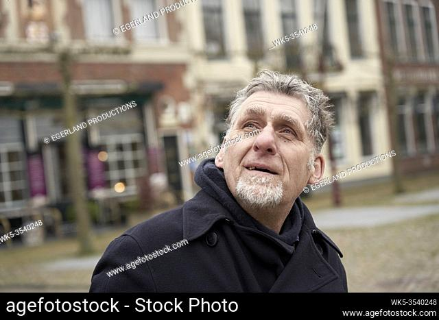 curious senior man peering up in Workum, Friesland, Netherlands