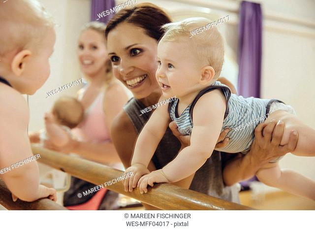 Mother holding up her baby to barre in dance studio