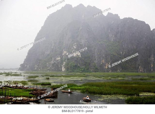 Rocky mountain over boats in rural marsh