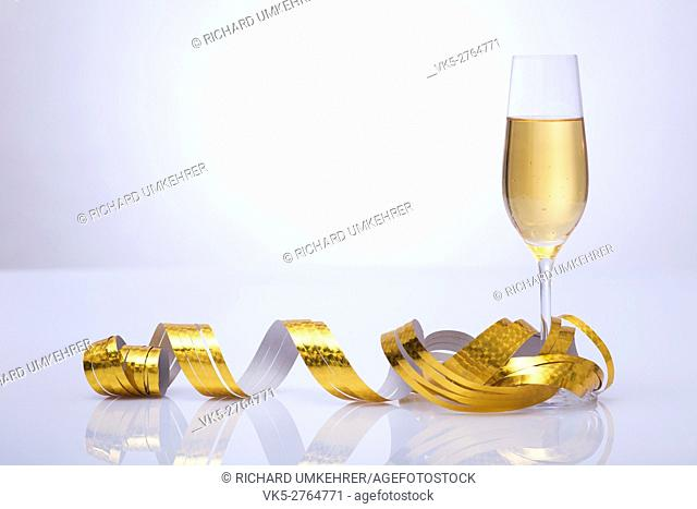 A glass of sparkling wine on a white table in front of white background. Glass is decorated with golden streamers. vignette background