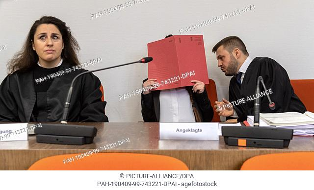 09 April 2019, Bavaria, München: At the beginning of the trial, the defendant sits in the courtroom between the lawyers Sera Basay-Yildiz (l) and Ali Aydin (r)...