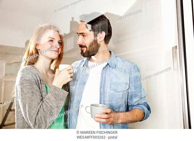 Smiling young couple having a coffee break behind windowpane