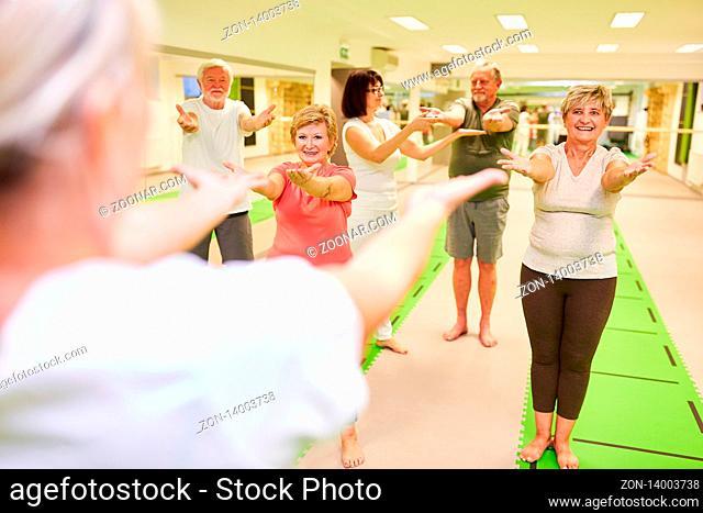 Senioren trainieren in einem Rückengymnastik Kurs in der Reha mit Trainer Betreuung