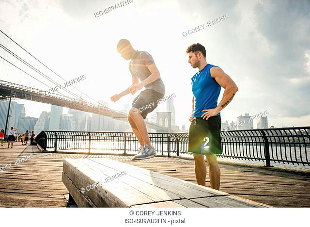 Personal trainer and young man training on riverside bench, Brooklyn, New York, USA