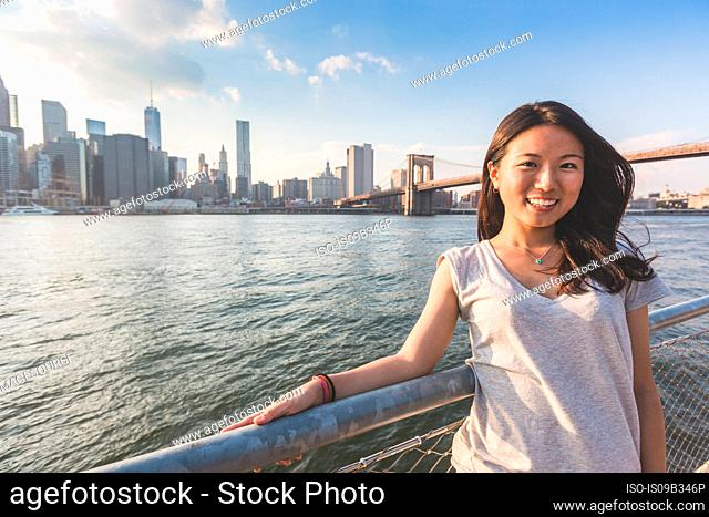 Portrait of young woman on ferry, Lower Manhattan and Brooklyn Bridge in background, New York City, New York, USA