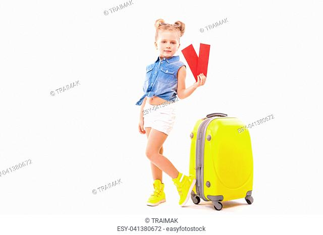 Isolated on white, little caucasian blonde girl in blue shirt, white shorts, sunglasses and sandals stand near the yellow suitcase
