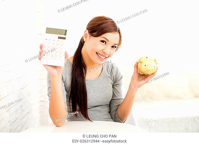Young Woman holding a calculator and piggy bank
