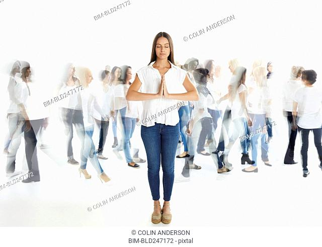 Portrait of woman standing out from the crowd and praying