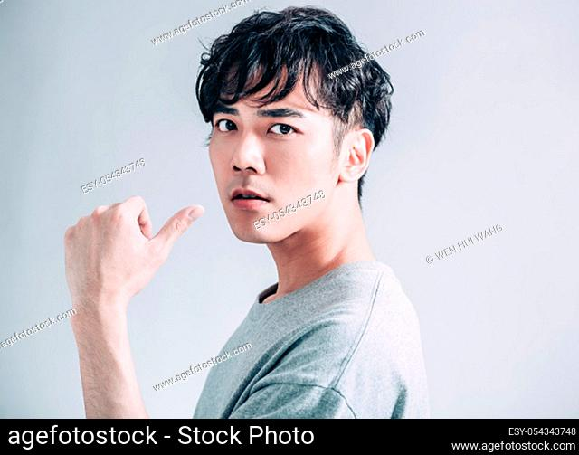 portrait of young asian handsome man isolated on gray background