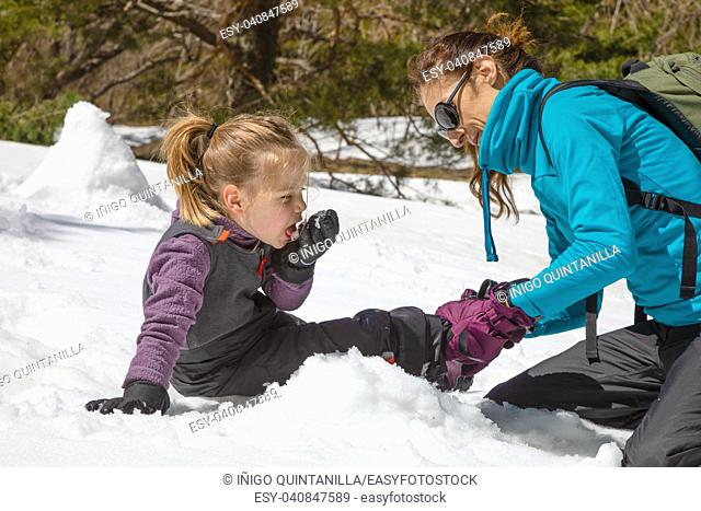 woman placing boot to her funny daughter, four years old blonde girl, sitting on the snow in nature. Child is eating snow with her hand