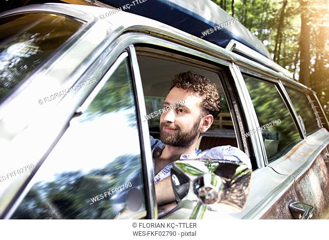 Smiling young man in car in forest